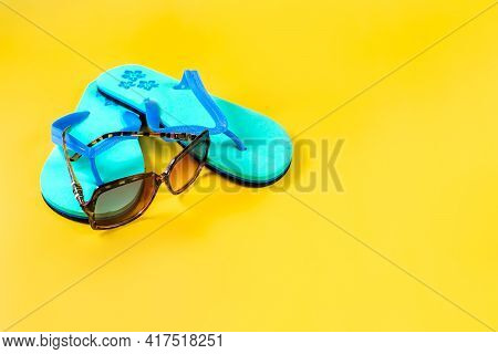 Beach Slippers, Flip-flops, Sunglasses On The Yellow Background. Summer Vacation Concept. Close-up.