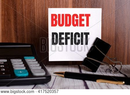 Budget Deficit Is Written On A White Card On A Wooden Background Next To A Calculator And Pen.