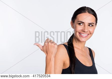 Photo Of Brunette Ponytail Haired Lady Point Look Empty Space Recommend Advert Isolated On Grey Colo