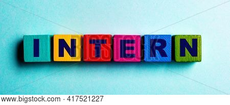 The Word Intern Is Written On Multicolored Bright Wooden Cubes On A Light Blue Background