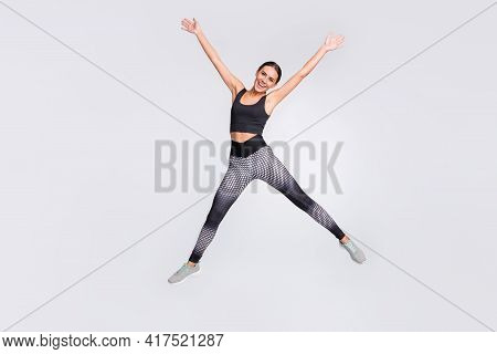 Full Length Photo Of Charming Cheerful Young Woman Jump Up Star Shape Sportive Isolated On Grey Colo