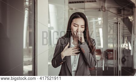 Young Asian women cough and cover their mouths with their hands to prevent drooling, young business