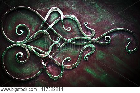 Iron Gate With Wrought Ornament On Dark Background