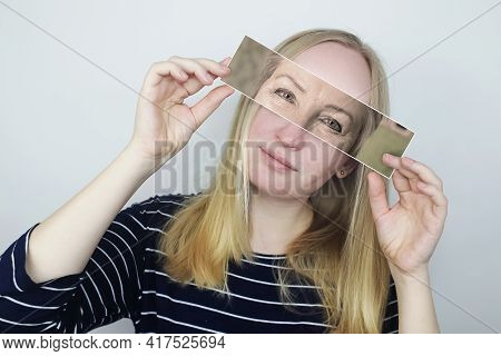 The Girl Holds A Photograph Of Her Old Mother To Her Face. Aging, Genetics, Family Tree And Loss Of