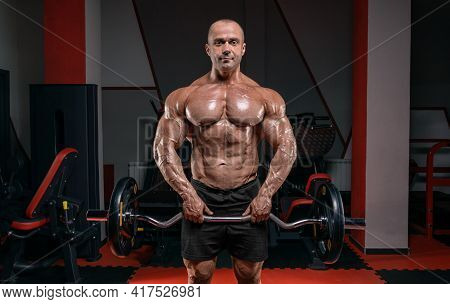 Powerful Bodybuilder Posing In The Gym With A Barbell. Bodybuilding Concept. Mixed Media