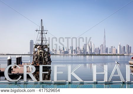 Dubai, Uae, 22.02.2021. Dubai Creek Harbour Sign With Black Pearl Pirate Ship By Tour With Dubai Dow