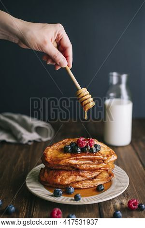 Hand With Honey Spoon Pours Honey Over Fried Bread Slices With Blueberries And Raspberries In An Old