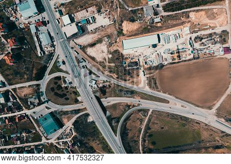 Aerial View Of An Industrial Area Infrastructure On The Outskirts Of The City. Highway, Cars, Buildi