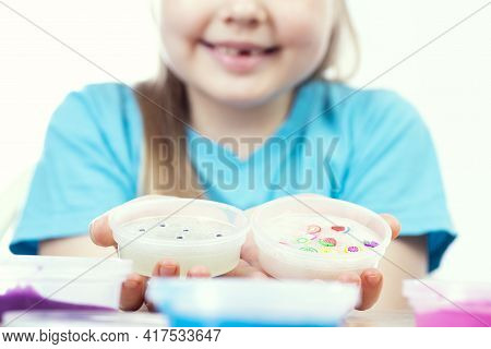 The Child Plays With Slimes. The Girl Shows Her Slimes In Her Hands. Play Slime Toy.