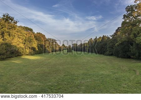 Beautiful Park With Landscaped Greenery. In The Background Is A Beautiful Sky