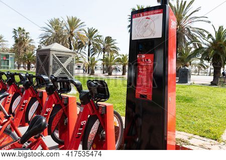 Barcelona, Spain - 1 April 2021 - Bike Station And Red Bikes On A Rack Available For Rent In Barcelo
