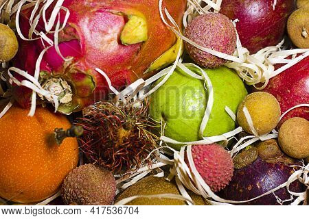 Different Tropical Fruits In Gift Box On Wooden Table. Different Tropical Fruits As Background, Clos