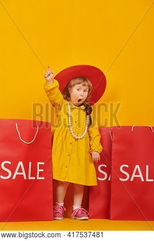 Emotional lovely little girl in a fashionable red hat and beads stands with shopping bags, raises her index finger up and wonders. Kid's fashion. Yellow background with copy space.