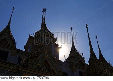 Sun Shining Through The Silhouette Of Loha Prasat  Spires, Wat Ratchanatdaram Temple, Historic Place