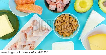 Ketogenic diet food. Low-carb food background, fish, meat, cheese, nuts, oil and butter on a blue background. mockup,  flatlay, flat lay Top view Keto diet concept.