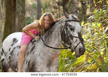 woman in pink dress in forest on horse