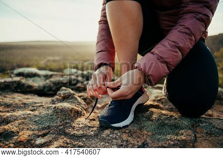 Close Up Caucasian Female Hiker Tying Shoe Lace While Walking Through Luscious Mountain
