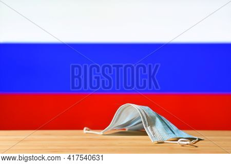 A Medical Mask Lies On The Table Against The Background Of The Flag Of Russia. The Concept Of A Mand