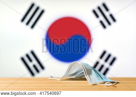 A Medical Mask Lies On The Table Against The Background Of The Flag Of South Korea. The Concept Of A