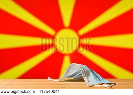 A Medical Mask Lies On The Table Against The Background Of The Flag Of North Macedonia. The Concept