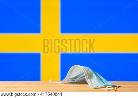A Medical Mask Lies On The Table Against The Background Of The Flag Of Sweden. The Concept Of A Mand