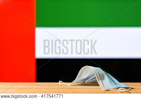 A Medical Mask Lies On The Table Against The Background Of The Flag Of Uae. The Concept Of A Mandato