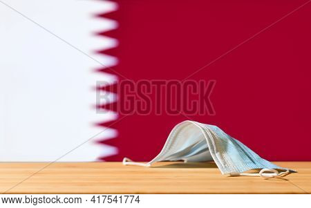 A Medical Mask Lies On The Table Against The Background Of The Flag Of Qatar. The Concept Of A Manda