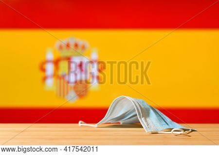 A Medical Mask Lies On The Table Against The Background Of The Flag Of Spain. The Concept Of A Manda
