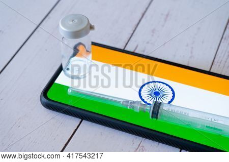 Mobile Phone With App Showing Indian Flag With A Syringe And Small Glass Bottle Vial Of Medicine Pla