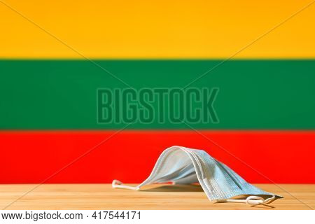 A Medical Mask Lies On The Table Against The Background Of The Flag Of Lithuania. The Concept Of A M