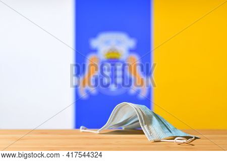 A Medical Mask Lies On The Table Against The Background Of The Flag Of Canary Islands. The Concept O
