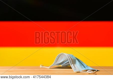 A Medical Mask Lies On The Table Against The Background Of The Flag Of Germany. The Concept Of A Man