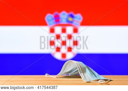 A Medical Mask Lies On The Table Against The Background Of The Flag Of Croatia. The Concept Of A Man