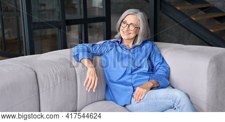 Mature Smiling Peaceful 60s Middle Age Lady Sitting On Couch Relaxing At Home. Senior Elder Serene W