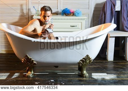 Shaving Man. Guy Shave With Razor In Bath In Bathroom. Macho With Shaving Soap On Beard Hair Look In