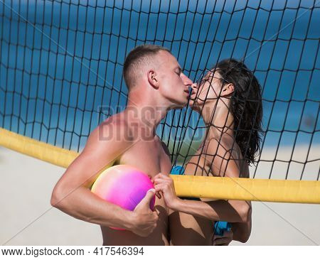 Woman And Man Doing Sport On Beach, Kissing. Young Sporty Active Couple Stand Near Volleyball Net, K