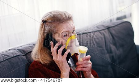 Elderly Woman Using Oxygen Inhaler While Speaking On The Phone. Coronavirus Outbreak And Vulnerable