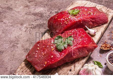 Raw Beef Steaks On A Wooden Cutting Board