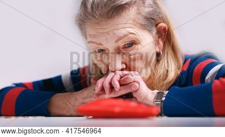 Hopeless Elderly Woman Looking At The Empty Wallet. High Quality Photo