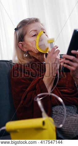 Vulnerable Old Woman In Quarantine Using Oxygen Inhaler And Changing Chanels On Tv. High Quality Pho