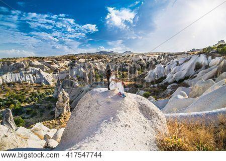 Goreme, Cappadocia, Turkey – 22 Oct 2020: Beautiful girl at amazing rocks in Zelve. Cappadocia Earth Pyramids. Turkey