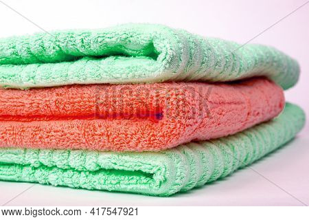 A Stack Of Green And Red Terry Towels Folded In A Stack