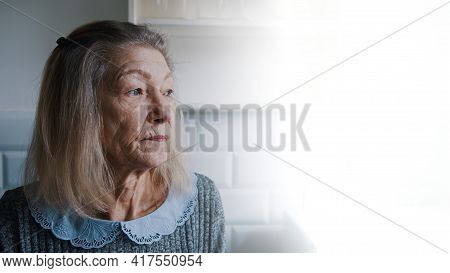 Sad Lonely Old Gray Haired Woman Looking Through The Window. Vulnerable Person In Quarantine. High Q