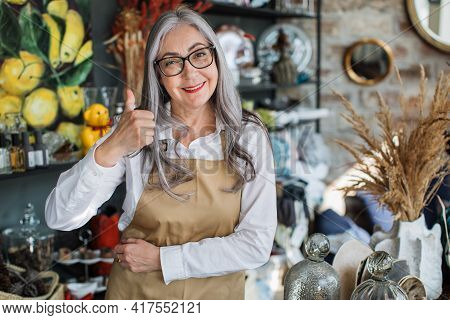 Mature Saleswoman In Eyeglasses Smiling And Showing Thumb Up While Posing At Modern Shop With Variou
