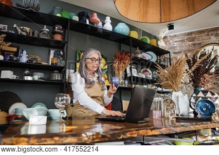 Experienced Saleswoman With Grey Hair Doing Inventory At Decor Store. Charming Lady Wering Eyeglasse