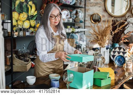 Attractive Aged Woman In Eyeglasses And Apron Doing Inventory At Decor Store, Opening Green Box. Com