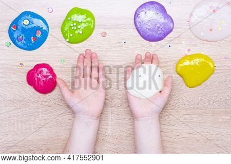 Multi-colored Slimes On The Table. The Child Plays With Slimes. Play Toy - Slime.
