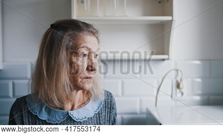 Portrait Of Elderly Gray Haired Lady Looking Through The Kitchen Window And Thinking. Vulnerable Lon