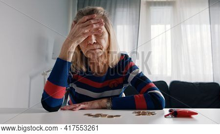 Worried Old Woman Running Out Of Money. Counting Coins On The Table. High Quality Photo