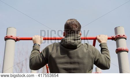 A Strong Guy Pulls Himself Up On A Horizontal Bar. A Man Pulls Himself Up On A Horizontal Bar In The